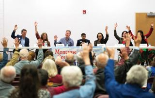 Democratic candidates for the U.S. Senate raise their hands, along with members of the audience, in response to a poll asking if President Donald Trump has committed enough questionable actions to warrant impeachment during a forum held at Centennial Middle School in Montrose Sunday. (William Woody/ Special to the Montrose Daily Press)